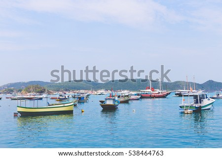 Colorful fishing boats in tropical turquoise water with mountain scenery in the background.