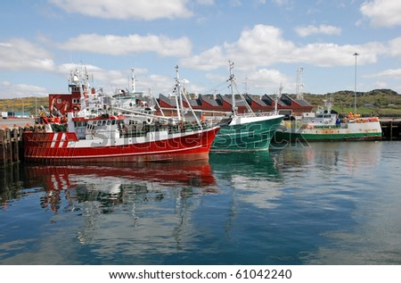 colorful fishing ships reflected in the water of an irish harbor in Donegal