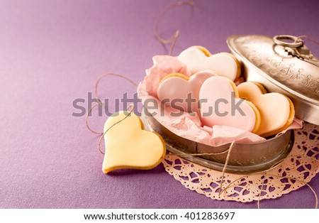 Colorful fondant heart shaped biscuits in a vintage tin to celebrate Valentines, anniversary, wedding or Mothers Day with a loved one or sweetheart, lilac background with copy space