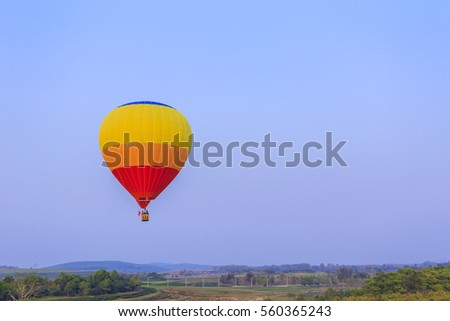 Colorful hot air balloon is flying at sunset
