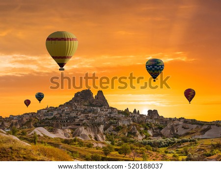 Colorful hot air balloons flying over the valley at Cappadocia, Uchisar, Turkey. Volcanic mountains in Goreme national park