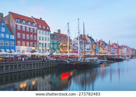 Colorful houses in Copenhagen old town, with boats and ships in the canal in front of them. Long exposure shot in late afternoon.