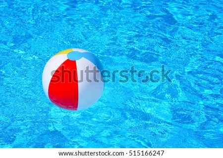 Colorful inflatable ball floating in swimming pool, summer vacation concept