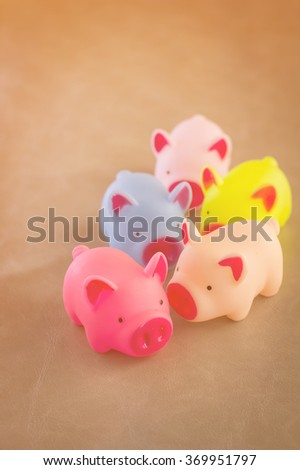 colorful of toy pigs stand on grey leather floor