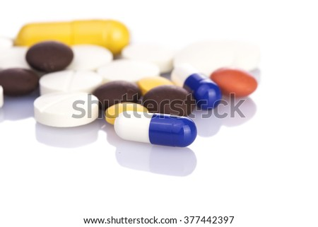 Colorful pills and capsules on white