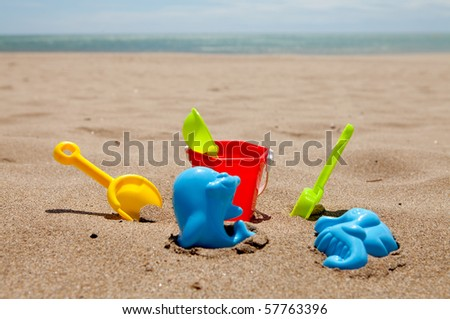 colorful plastic toys on the beach near the sea
