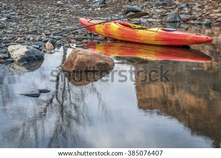 colorful river kayak with a paddle on rocky shore with a tree reflection - recreation concept