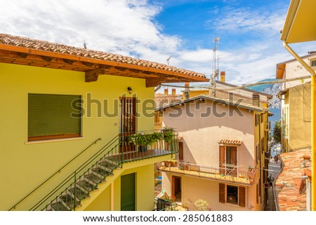 Colorful traditional Italian hotel balcony with view on old town and mountain lake