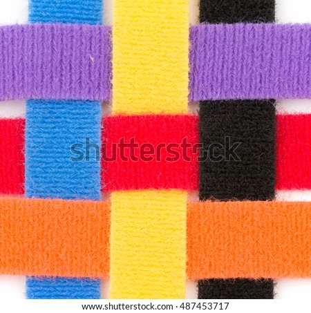 Colorful velcro strips braided together in over one, under one sequence, on white