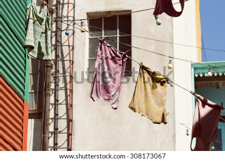 Colorful vintage clothing hanging to dry on a line under the sun in La Boca, Buenos Aires, Argentina.