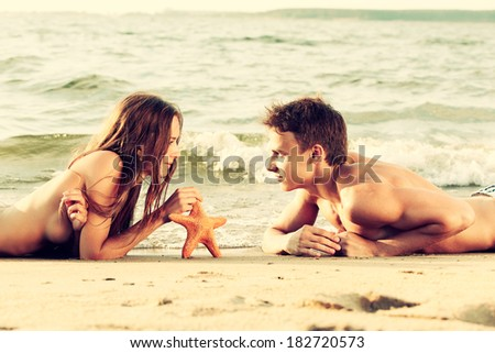 Colorized vintage outdoor portrait of  beautiful romantic couple of topless girl and muscular guy in jeans laying face to face with asteroid on beach