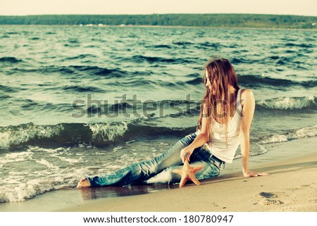 Colorized vintage outdoor portrait of outdoor portrait of beautiful girl in jeans posing on beach with asteroid
