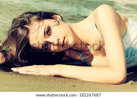 Colorized vintage outdoor portrait of Young beautiful slavonic girl laying on the sand