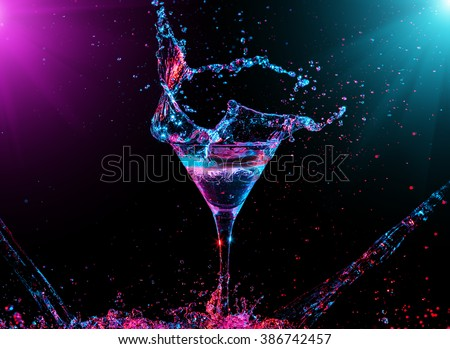 Colourful cocktail in glass with splash on the dark background