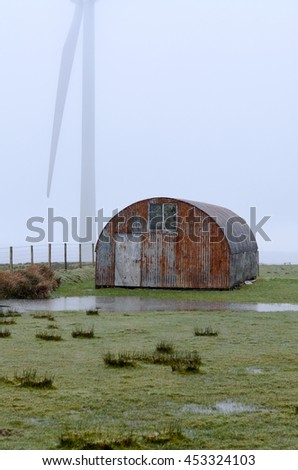 Colourful farm shed in heavy rain with blurred of wind turbine background.
