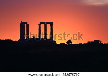 Columns of ancient Poseidon temple and red sunset sky in the background, Cape Sounio, Greece