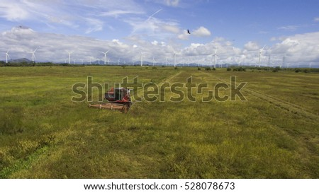 Combine machine harvesting rice in a rice field near a wind turbine farm in the heartland of Panama