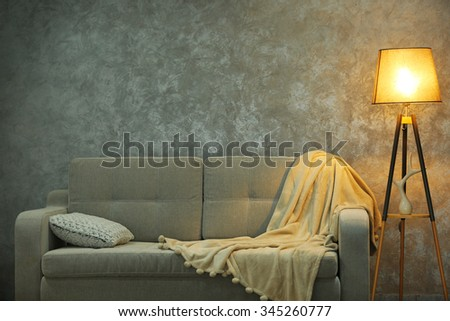 Comfortable sofa and lamp on grey wall background