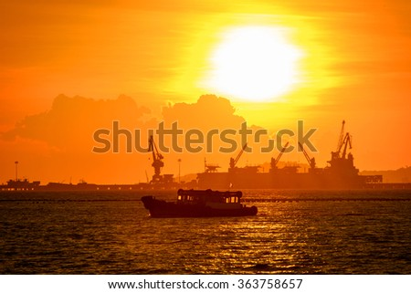 commercial dock with ship and cranes in sunset
