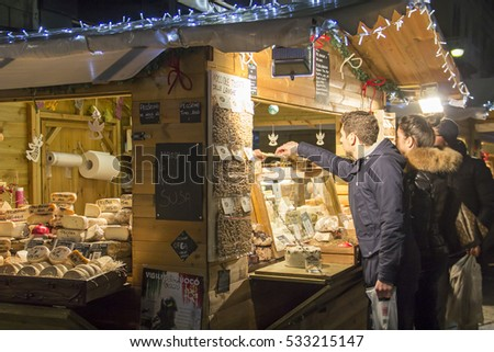 COMO, ITALY - DECEMBER 2, 2016: People buy italian cheese at winter Christmas market