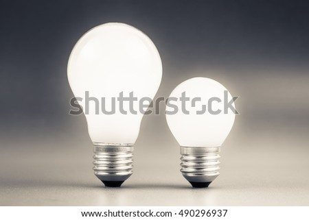 Comparative big and small light bulb, small and medium sized business, coaching, training, or other comparison concept