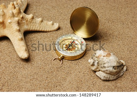 compass and starfish on a sandy beach
