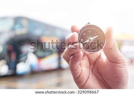 Compass in hand on blur of bus for background