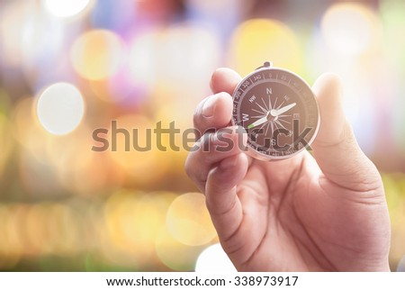 compass in hand on defocused abstract bokeh lights christmas background, blur of bokeh circle light christmas festive backdrop concept.