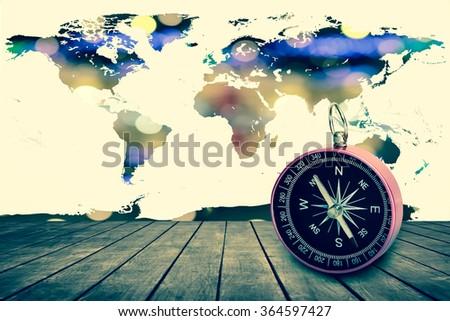 compass on old perspective wooden floor with world map on bokeh light  background