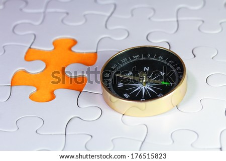 Compass on puzzle with one piece missing