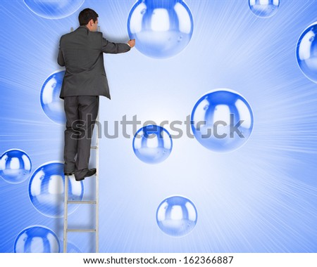 Composite image of businessman standing on ladder writing