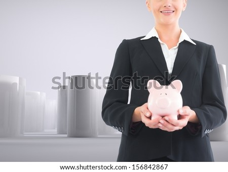 Composite image of businesswoman holding piggy bank in front of 3d cylinders