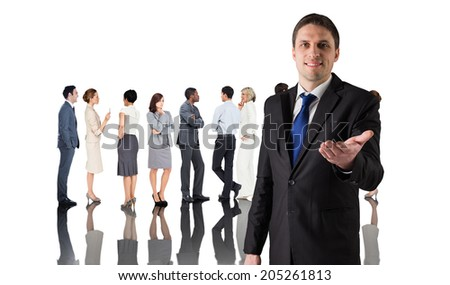 Composite image of handsome businessman holding hand out against group of workers