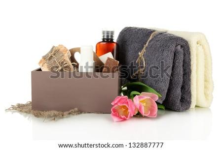Composition of cosmetic bottles and soap in crate, isolated on white
