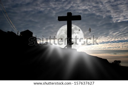Composition with a stone cross against a beautiful moonrise sky.