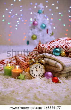 Composition with plaids, candles and Christmas decorations, on white carpet on bright background