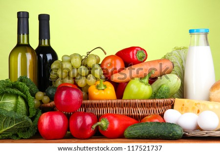 Composition with vegetables  in wicker basket on green background