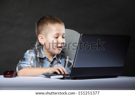Computer addiction child boy with laptop notebook black background