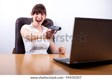 Computer error/problem. Young businesswoman losing her temper and about to shoot her laptop.