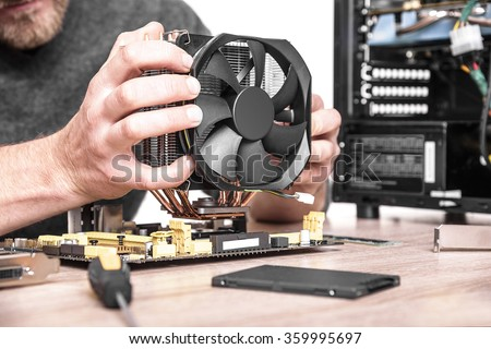 Computer technician installs cooling system of computer.