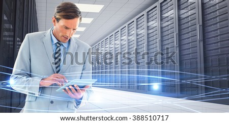 Concentrate businessman using tablet pc against blue lines and lights on black background