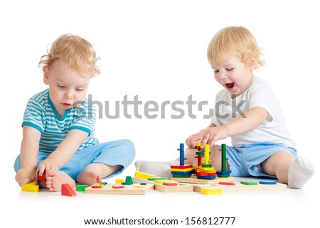 Concentrated child playing logical education toys with great interest on white background