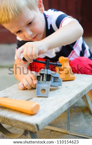 Concentrated little boy is playing in carpenter