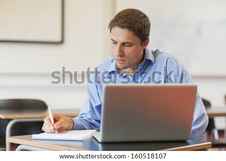 Concentrated male mature student using his notebook for learning while sitting in classroom