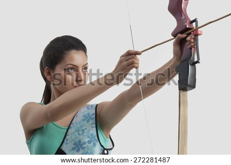 Concentrated woman practicing archery against gray background