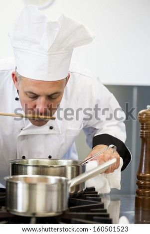 Concentrating head chef tasting sauce with wooden spoon in professional kitchen