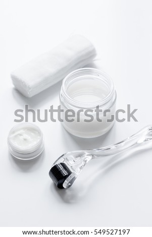 concept cosmetologist desktop with mezoroller - mesotherapy on white background