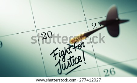 Concept image of a Calendar with a golden dart stick. The words Fight for Justice written on a white notebook to remind you an important appointment.