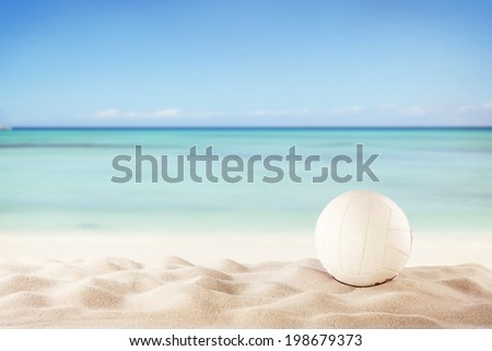 Concept of beach volleyball with ball on sand, blur sea as background