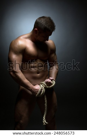 Concept of bodybuilding. Nude man with torn rope